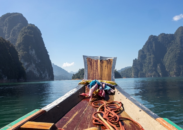 Boat on the water surrounded by cliffs in khao sok national park, thailand