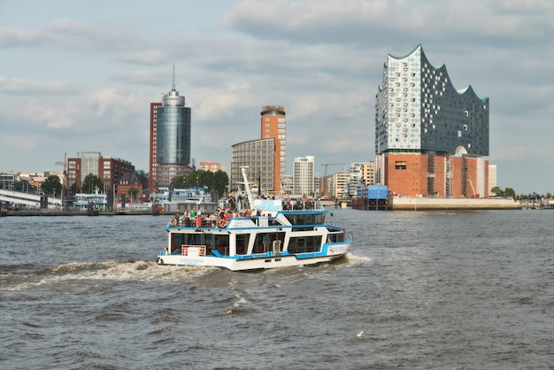 Boat with tourists goes on elbe river towards elbphilharmonie in hamburg
