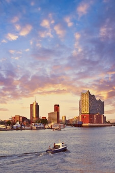 Boat with tourists goes towards elbphilharmonie in hamburg at sunset