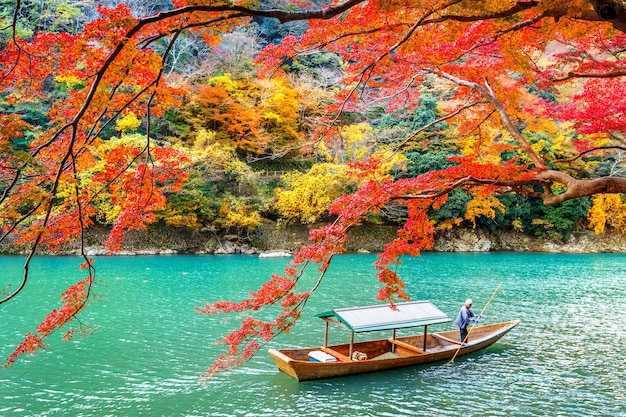 Boatman punting the boat at river. arashiyama in autumn season along the river in kyoto, japan.