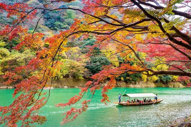 ボートマンが川でボートをパントします。京都の川沿いの秋の季節の嵐山。