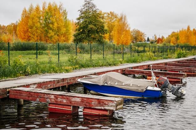 曇り空の午後の秋の桟橋でのボート