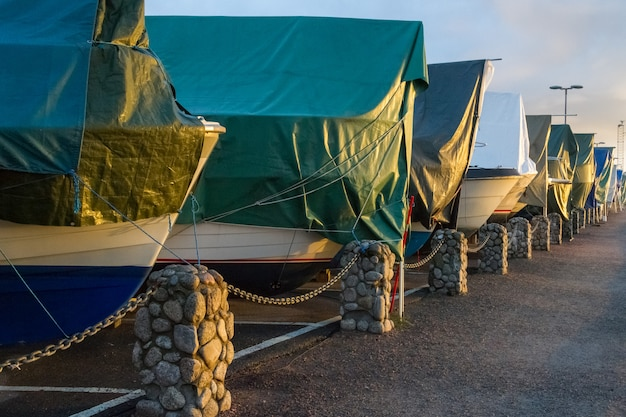 冬の貯蔵でターポリンで覆われたボート