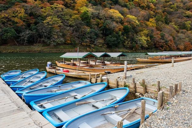 Boats at dock on katsura river with fall colors in arashiyama, kyoto, japan