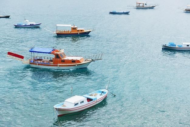 Boats float in the calm blue sea water in turkey.