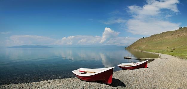 Лодки на берегу озера хубсугул, туризм в монголии. летний отдых на воде.