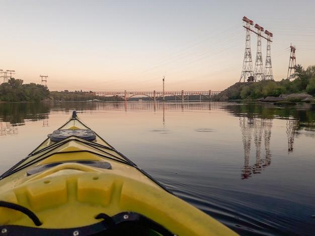 日没の電気の塔と背景のテキストスペースの休暇旅行の橋で川のボート