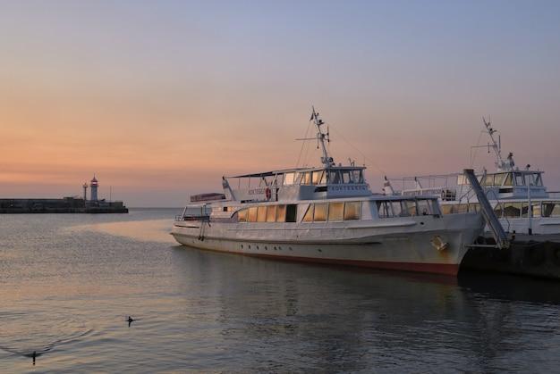 Лодки на набережной ялты рано утром в маяке розового света
