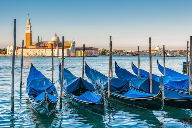 ヴェネツィアの水に停泊しているボートと背景のサンジョルジョマッジョーレ教会