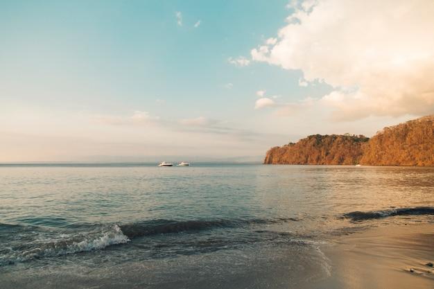 海の背景の夕方の光で沿岸の丘でセーリングボート