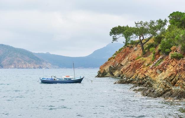 トルコの山の近くの穏やかな青い海の水でセーリングボート。
