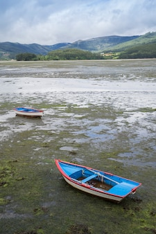 Boats stranded at the mouth of a river at low tide