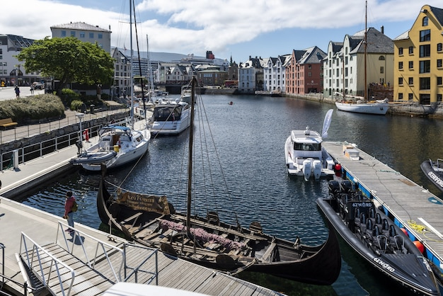 Boats on a wide water canal surrounded by colorful buildings in alesund, norway