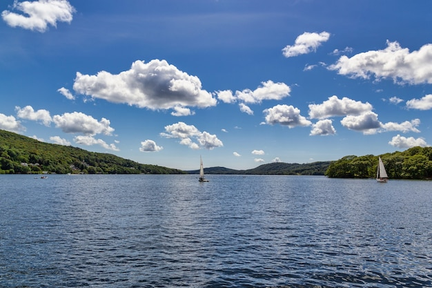 Boats in the windermere lake with little fluffy clouds above