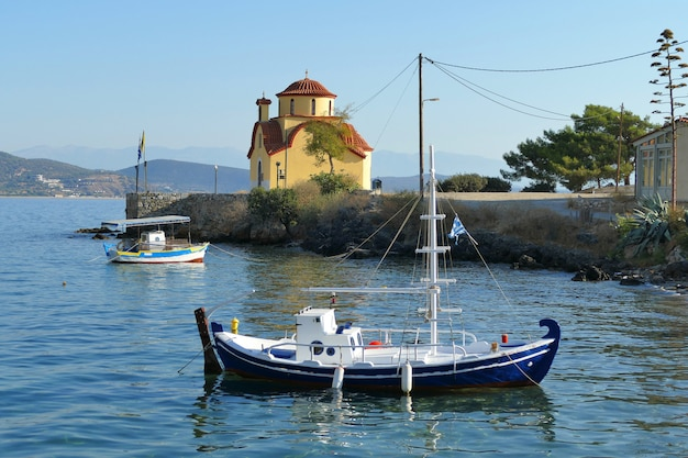 Boats with an orthodox church in the background in the port of gythio
