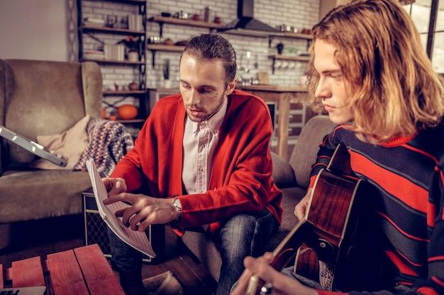 Боб отрезал. светловолосый талантливый трудолюбивый музыкант с короткой стрижкой слушает своего коллегу
