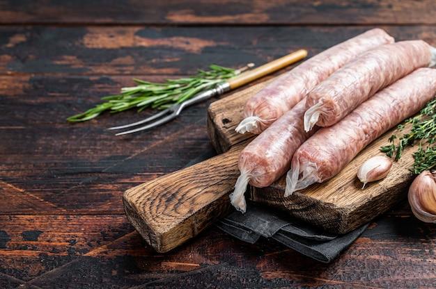 Bockwurst 나무 판자에 돼지고기를 넣은 생 소시지. 어두운 나무 배경입니다. 평면도. 공간을 복사합니다.