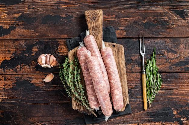 Bockwurst 나무 판자에 돼지고기를 넣은 생 소시지. 어두운 나무 배경입니다. 평면도.
