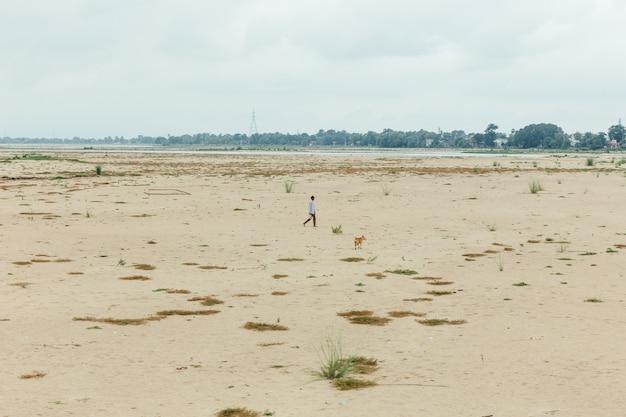 男と犬のbodh gaya、ビハール州、インドのmahabodhi寺院近く干潮時に歩いています。