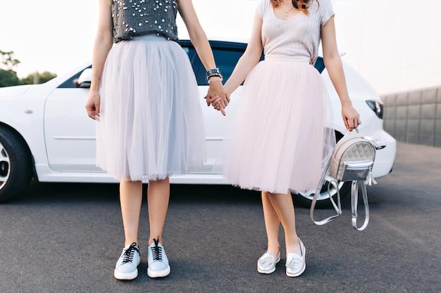 Corpi di modelle in gonne di tulle e scarpe da ginnastica su macchina bianca. si tengono per mano.