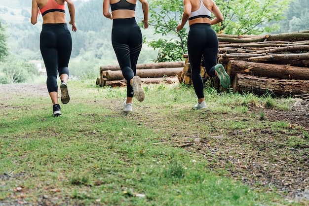 Bodies of a three women running through a green forest with lots of trees