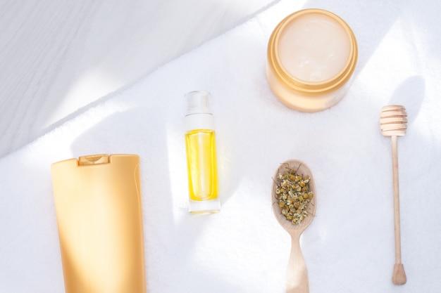Средства по уходу за телом и волосами, туалетные принадлежности с полотенцем, солнечный свет. уход и чистая концепция для кожи, волос и тела. плоская планировка, копирование пространства.