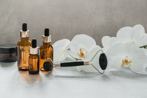 난초 꽃이 있는 욕실의 바디 및 스킨 케어 제품, 스포이드 병, 흑요석 스톤 구아샤 마사지 롤러, 스파 화장품 브랜드 모형