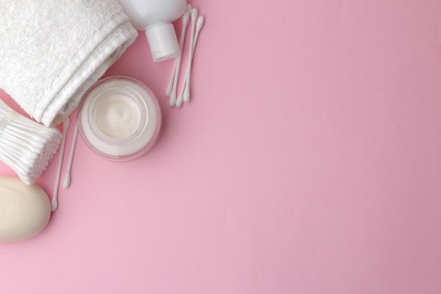 분홍색 테이블에 흰색 포장의 바디 및 스킨 케어 제품