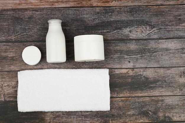 木材の背景に白い包装で体とスキンケア製品。個人用衛生用品。上からの眺め。テキスト用のスペースあり