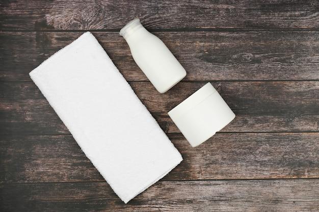 ウッドスペースにホワイトパッケージのボディ&スキンケア商品。個人用衛生用品。 。テキスト用のスペースあり
