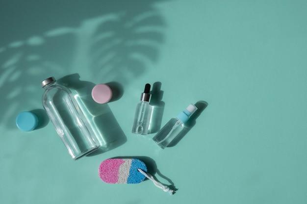 ボディとスパのトリートメント。ナチュラルビューティー製品。エコクリーム、美容液、スキンケア用の空のボトル。ガラスピペット。足用軽石。上面図。ヤシの木からの影
