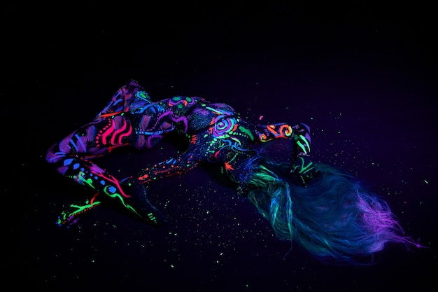 Body art on body dancing in ultraviolet light