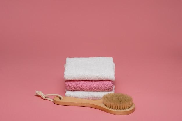분홍색 배경에 부드러운 수건으로 셀룰 라이트 방지 마사지 및 피부 트리트먼트를위한 바디 브러시. 복사 공간이있는 디자인을 배치합니다. 스파 개념.