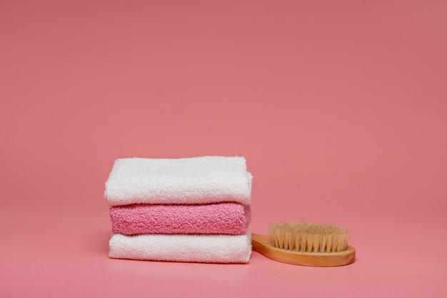 ピンクの背景に柔らかいタオルでアンチセルライトマッサージとスキンケアのためのボディブラシ。コピースペースでデザインをレイアウトします。スパのコンセプト。