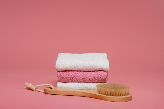 분홍색 배경에 부드러운 타월로 안티 셀룰 라이트 마사지 및 피부 트리트먼트를위한 바디 브러쉬