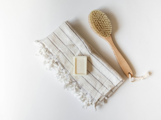 Body brush with wooden handle, white towel and  piece of soap on a white background.