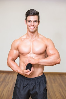 Body builder holding bottle with supplements in gym
