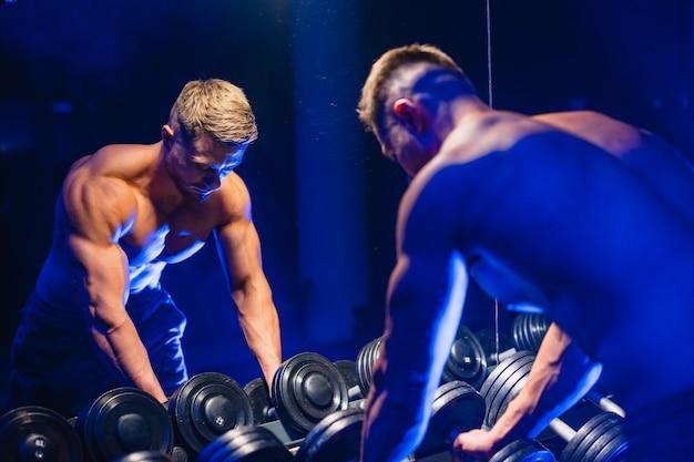 체육관에서 운동하는 바디 빌딩 챔피언, 아래를 내려다 보면서 포즈를 취하는 아령으로 거울 앞에 서서