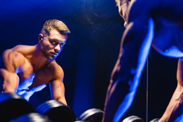Чемпион по бодибилдингу тренируется в тренажерном зале, стоя перед зеркалом с гантелями, позирует, глядя прямо