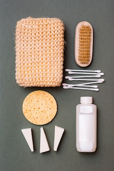 Уход за телом. набор для ванной - мочалка, шампунь, губки, ватные палочки и кисточка на зеленом фоне. вертикальный вид