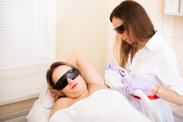 Body care. beautiful girl lies in the office of a beautician in goggles from laser irradiation, the hands of the doctor remove hair on hands with a laser device