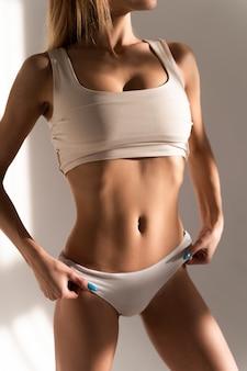 바디 케어. 맞는 슬림 바디, 흰색 비키니에 건강하고 부드러운 부드러운 피부와 모양의 아름다운 여자