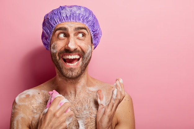 바디 케어 개념. 행복한 남자는 샤워를하고, 스트레스를받은 작업 후 이완하고, 거품으로 젖은 피부를 가지고 있으며, 스폰지로 가슴을 문지르고, 즐겁게 옆으로 보이며, 분홍색 벽에 고립되어 있습니다.