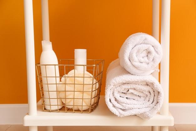 Косметика по уходу за телом с аксессуарами на полке в ванной комнате