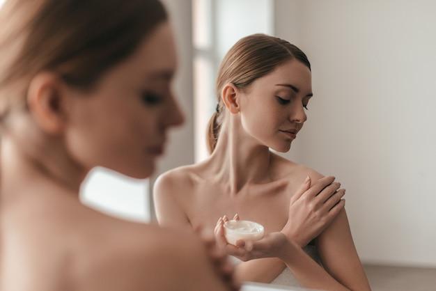 Уход за телом. вид через плечо привлекательной молодой женщины, намазывающей крем по телу, стоя перед зеркалом