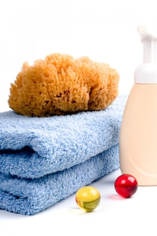 Body care products and towel on white background