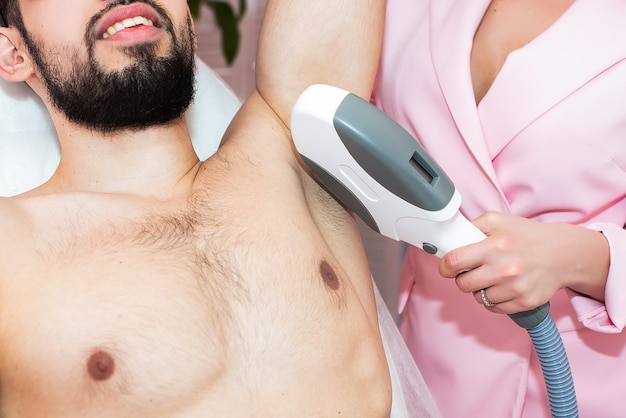 Body care. underarm laser hair removal. beautician removing hair of men's armpit. in cosmetic beauty clinic.
