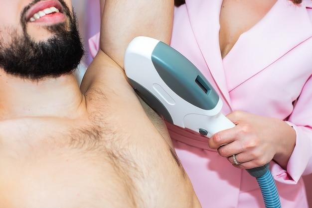 Уход за телом. лазерная эпиляция подмышек. косметолог удаления волос мужской подмышки. в косметической клинике красоты.