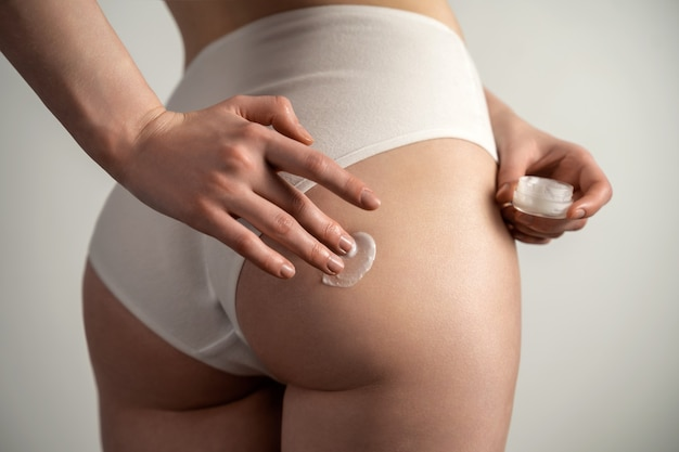 Body care woman applying cream on legs and buttocks girl in a black thong athletic studio shot on a blue background
