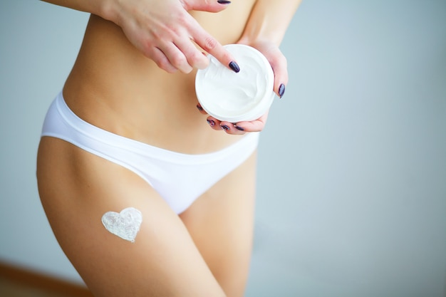 Body care. woman applying moisturizer cream on legs.